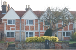 The proposed new building will loom over the medieval cottages